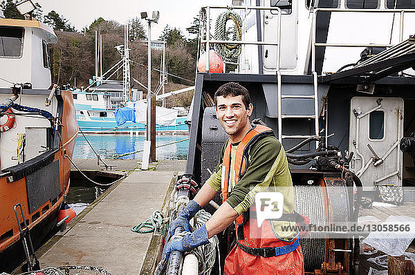 Portrait of happy fisherman standing on fishing boat