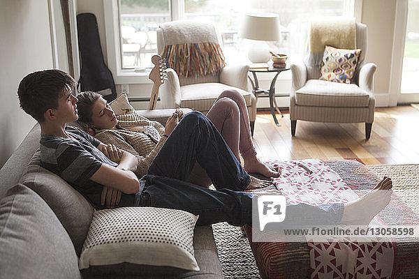 Hochwinkelansicht von Geschwistern  die sich zu Hause auf dem Sofa entspannen