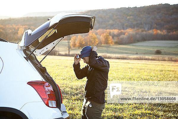 Seitenansicht eines Mannes  der einen Scheinwerfer trägt  während er im Auto auf dem Feld steht