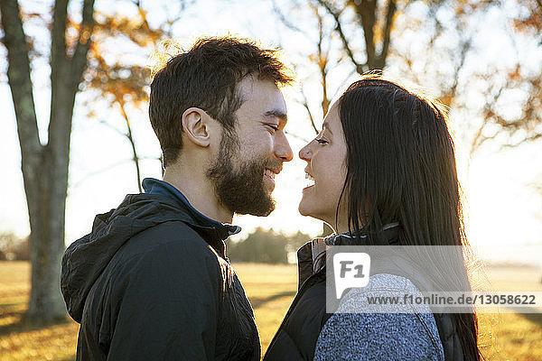 Seitenansicht eines fröhlichen Paares  das auf dem Spielfeld steht