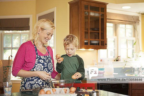 Glückliche Mutter und Sohn bereiten zu Hause in der Küche Essen zu