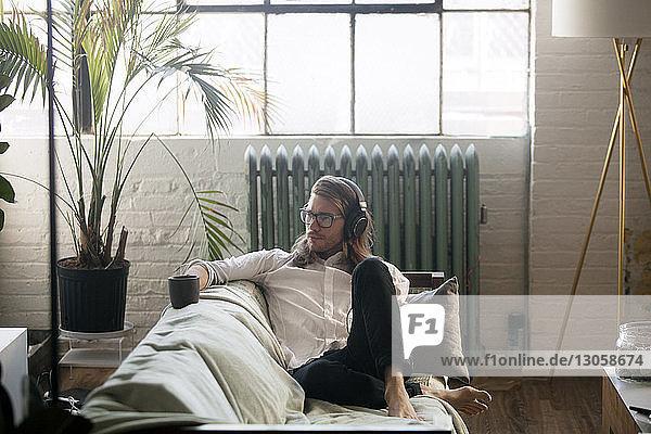 Nachdenklicher Mann hört Musik  während er zu Hause auf dem Sofa sitzt