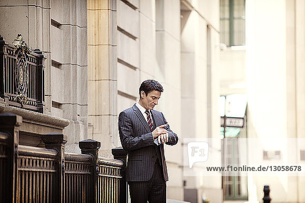 Businessman checking the time while standing on city street