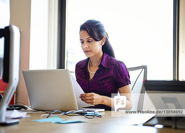 Woman working on laptop at desk in creative office