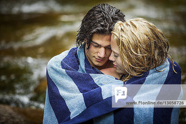 Affectionate couple wrapped in towel