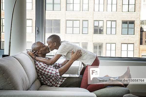 Couple kissing while sitting on sofa at home