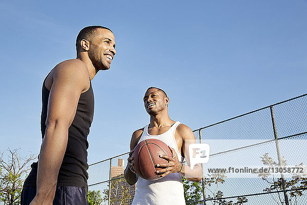 Low angle view of happy basketball players while standing in court against clear sky
