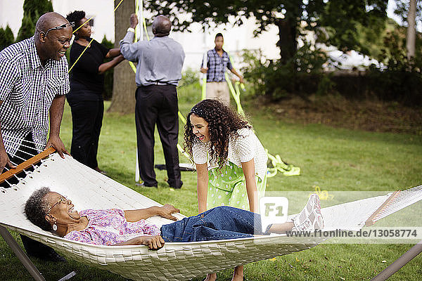 Happy girl looking at senior woman lying in hammock with family in background at backyard