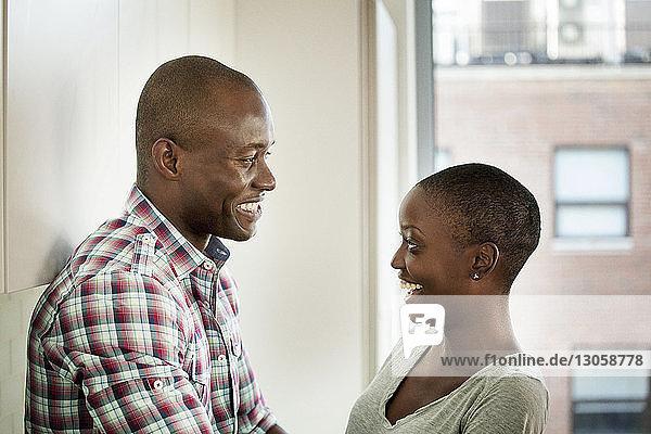Fröhliches Paar redet  während es zu Hause an der Wand steht