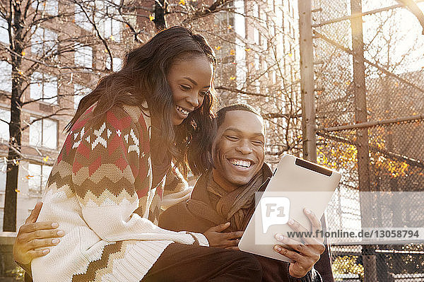 Happy young couple looking at digital tablet against buildings