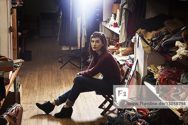 Portrait of confident woman sitting on chair at clothing store