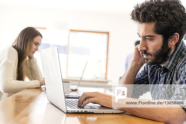 Man and woman using laptop while sitting at table
