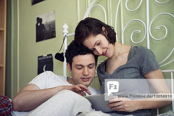 Glückliches Paar schaut sich zu Hause ein digitales Tablett auf dem Bett an