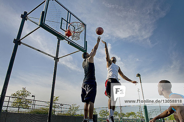 Niedrigwinkelansicht von Sportlern  die Basketball vor Gericht gegen den Himmel spielen