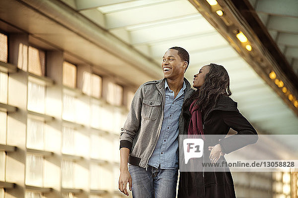 Low angle view of cheerful couple standing in covered walkway