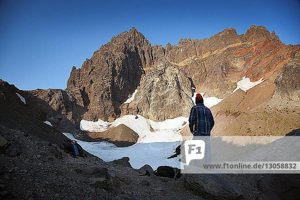 Rear view of hiker looking at mountains during winter