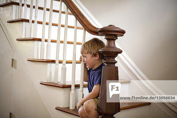 Boy crying while sitting on staircase at home