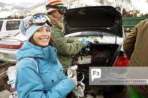 Happy friends removing skiing equipment from car