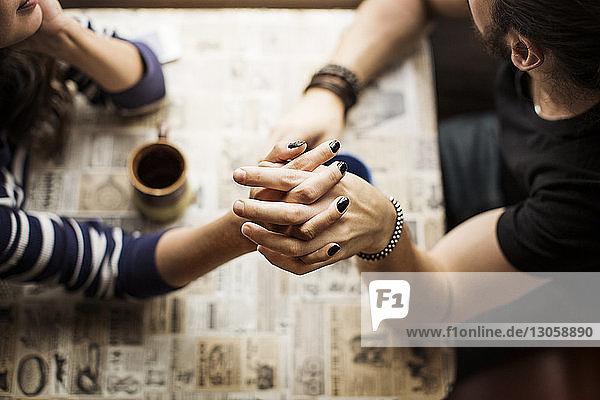 Draufsicht auf ein junges Paar  das die Hände auf dem Tisch hält