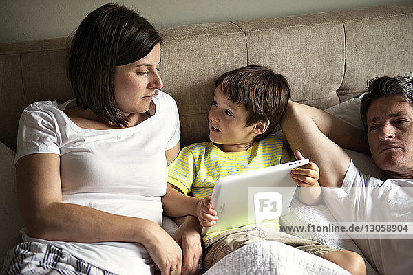 Boy using tablet computer while lying with parents on bed at home