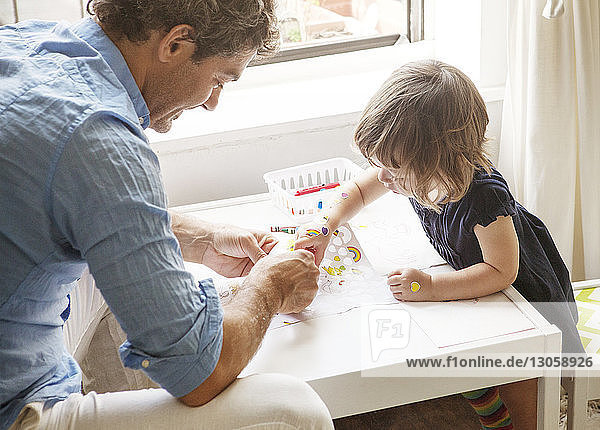 Hochwinkelaufnahme von Vater und Tochter beim Ausmalen bei Tisch zu Hause