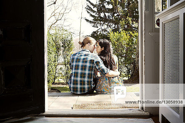 Rear view of couple sitting on front stoop