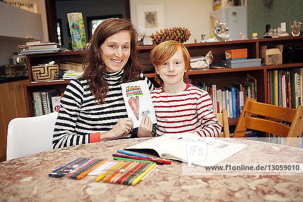 Porträt von Mutter und Sohn  die eine Karte halten  während sie auf einem Stuhl am Tisch sitzen