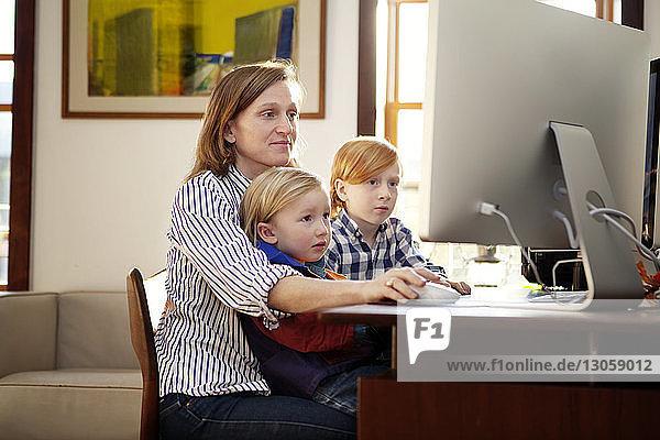 Mutter benutzt Desktop-Computer  während sie mit Kindern zu Hause sitzt
