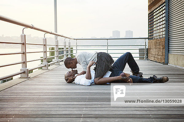 Side view of affectionate couple lying on floorboard at pier