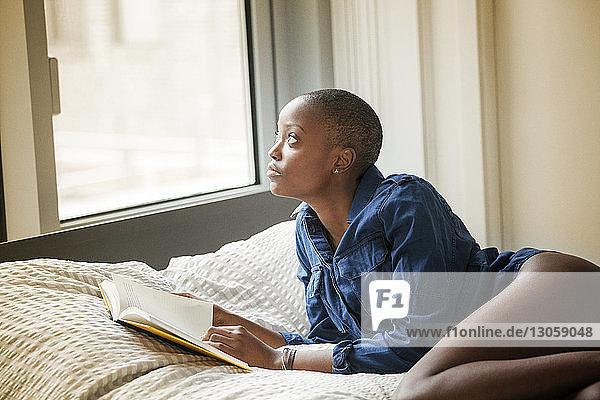 Frau schaut weg  während sie zu Hause ein Buch in der Hand hält