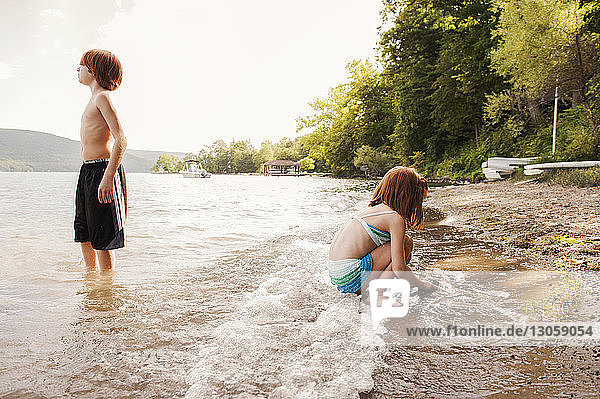 Girl playing at shore while brother standing in lake