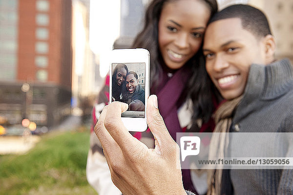 Happy young couple clicking selfie with smart phone