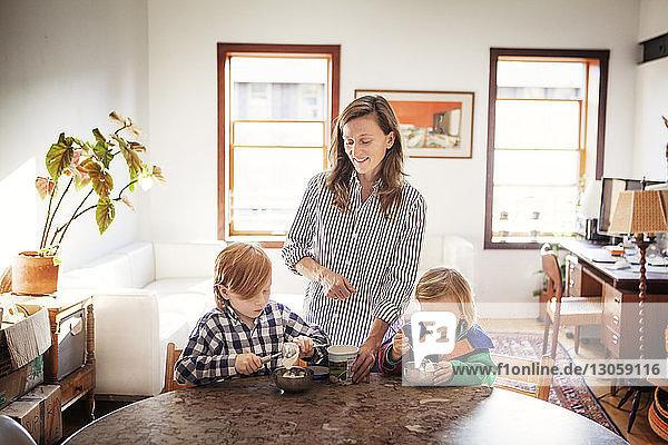 Kinder essen Eis  während die Mutter zu Hause am Esstisch steht