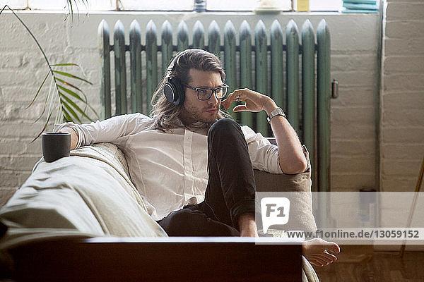Mann schaut weg  während er Musik über Kopfhörer hört