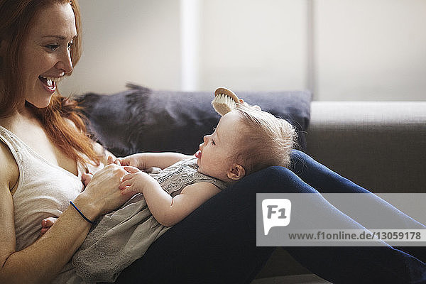Cropped image of mother brushing baby girl's hair while sitting on sofa at home