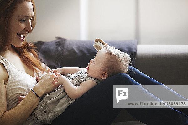 Ausgeschnittenes Bild einer Mutter  die zu Hause auf dem Sofa sitzend die Haare des Mädchens bürstet