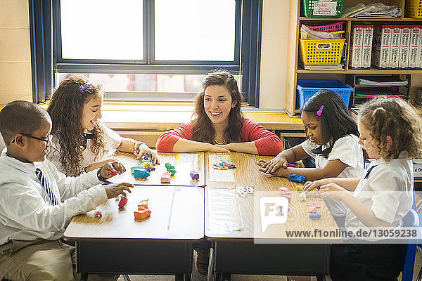 Happy teacher looking at students molding clay at desk in classroom