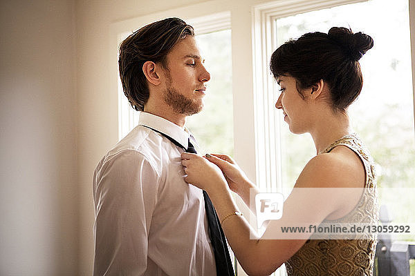 Frau bindet die Krawatte ihres Freundes