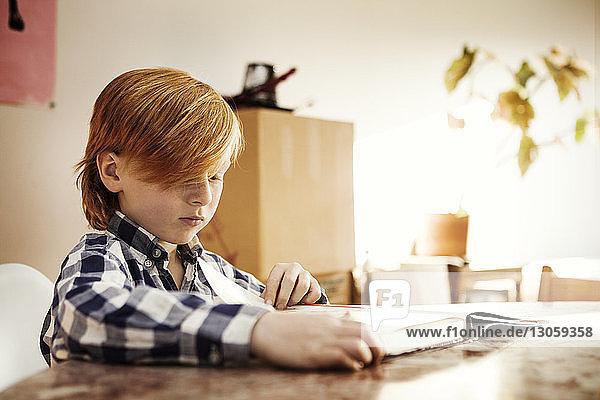 Junge liest Buch  während er zu Hause am Tisch sitzt