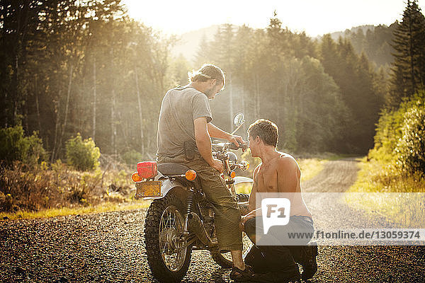 Friends with motorcycle on gravel road