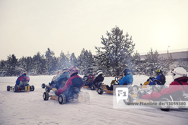 Teenagers enjoying go-carts racing on snow covered field