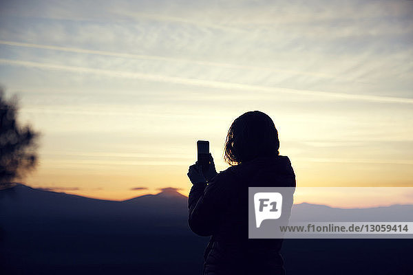 Silhouette woman photographing with smart phone against sky during sunset