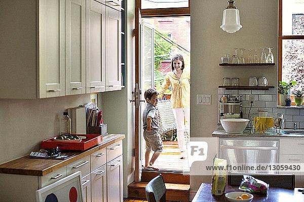 Happy mother looking at son seen through kitchen door