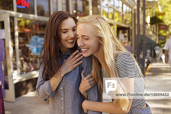 Freunde lachen  während sie auf der Straße der Stadt stehen