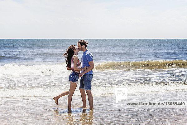 Zärtliches Paar küsst sich  während es am Strand am Ufer steht
