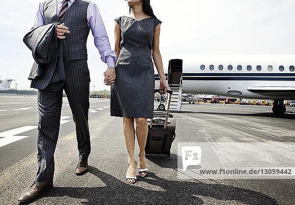 Niedriger Teil eines Geschäftspaares  das beim Gehen auf der Startbahn des Flughafens Händchen hält