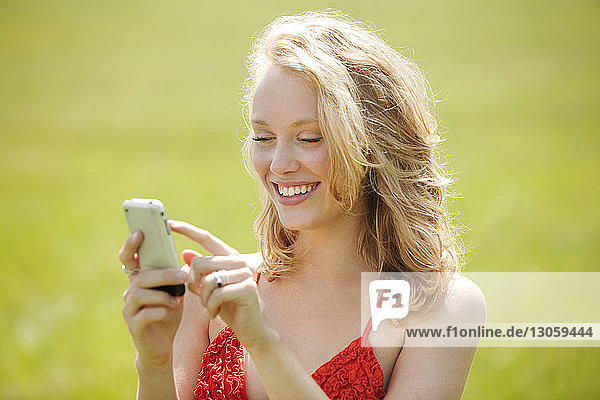 Woman using smart phone while standing in field