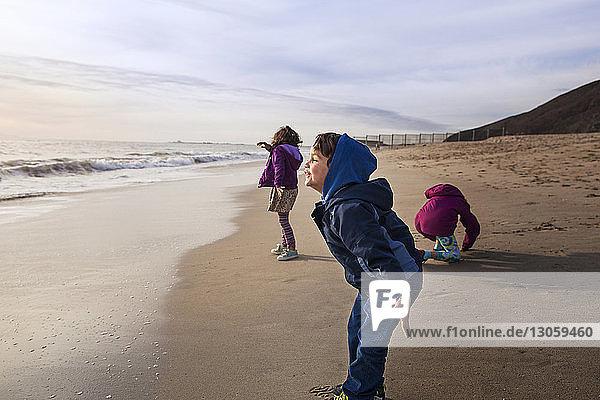 Sibling enjoying at beach against cloudy sky