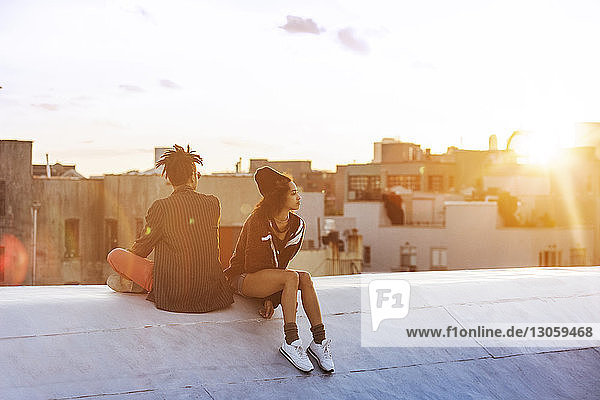 Auf Stützmauer gegen Gebäude sitzendes Ehepaar
