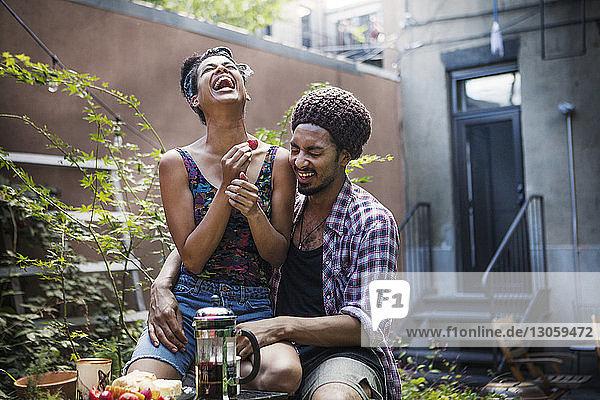 Fröhliches Paar am Frühstückstisch auf dem Rasen